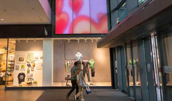 Et ungt par beundrer et changerende Luminous Textile-panel i shoppingcenteret Centrum Galerie